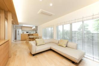 隣家の建物に挟まれ光が入りにくい家を、どの部屋も明るく暖かで、木のぬくもりあふれ